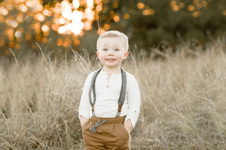 A small boy stands with his hands in his pockets.
