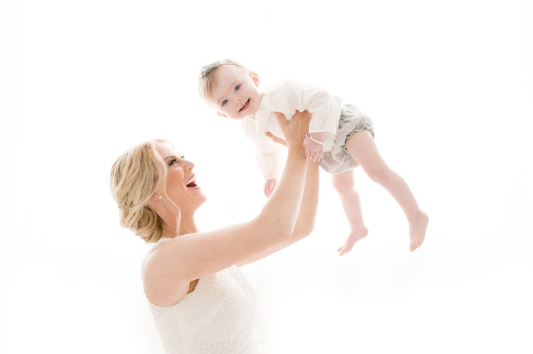 A mother lifts her daughter up into the air.
