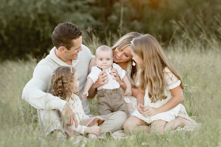 A family sits together in a field.