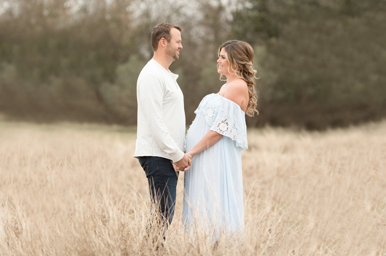 A couple hold hands with a pregnant belly between them.   Houston Maternity Photographer