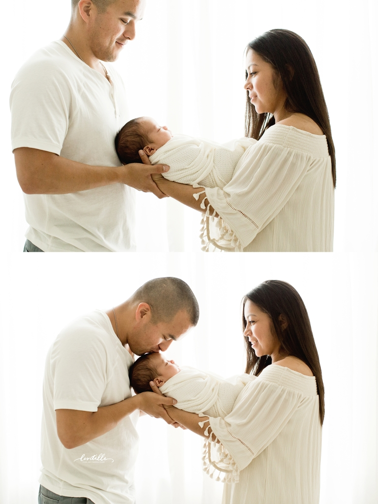 A mother hands her baby to his dad