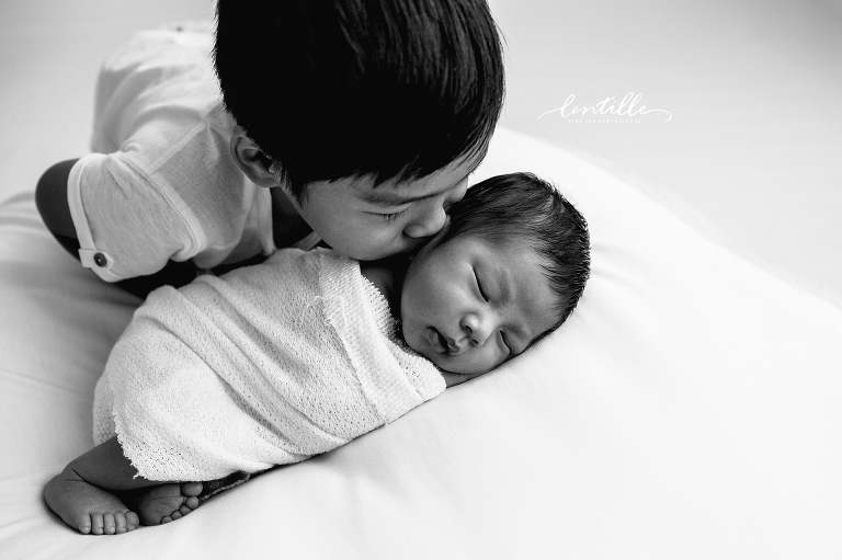 Big brother kissing baby by Lentille Photography