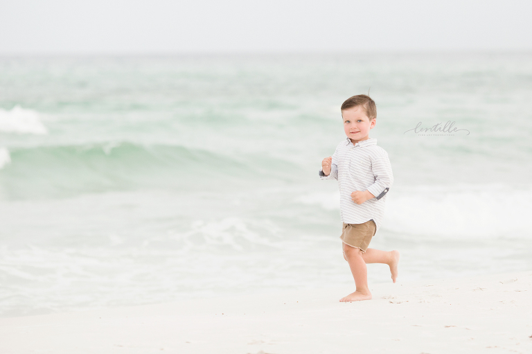 Little boy running on the beach taken by a Houston Family Photographer