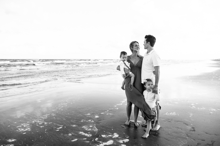 A family standing on the beach, taken by a Houston Family Photographer