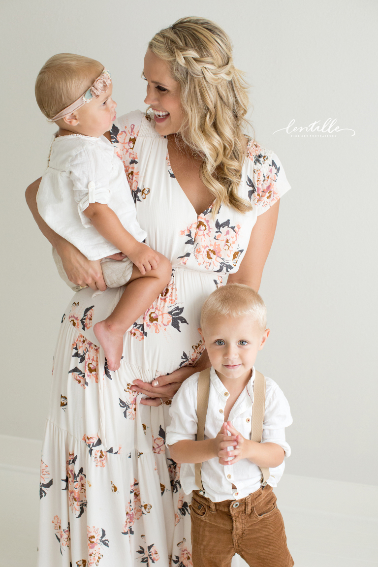 A mother snuggles her children, taken by a Houston Family Photographer