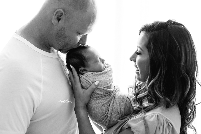 A father kisses his baby taken by a photographer who focuses on Houston Newborn Photography
