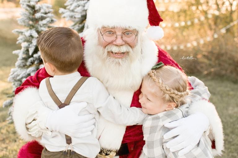 Two children hug Santa