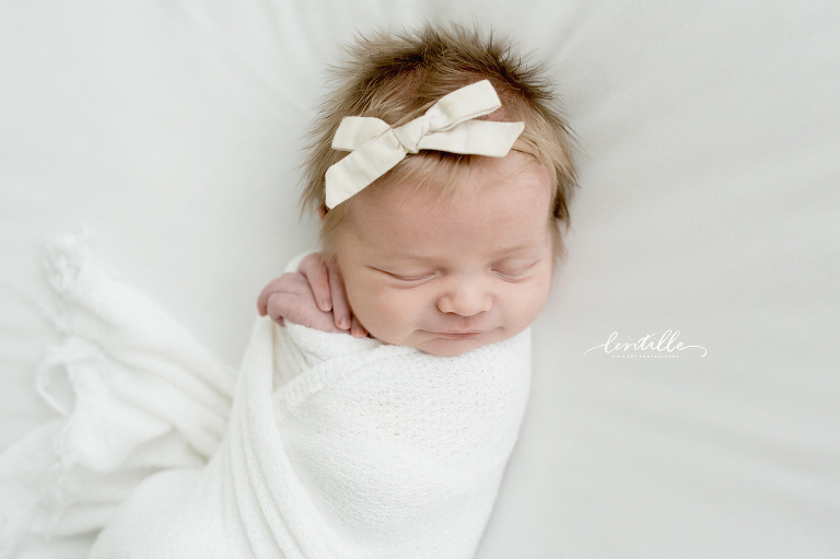 A baby girl wears a white bow, taken by the photographer at Lentille Photography, who specializes in Houston Newborn Photography