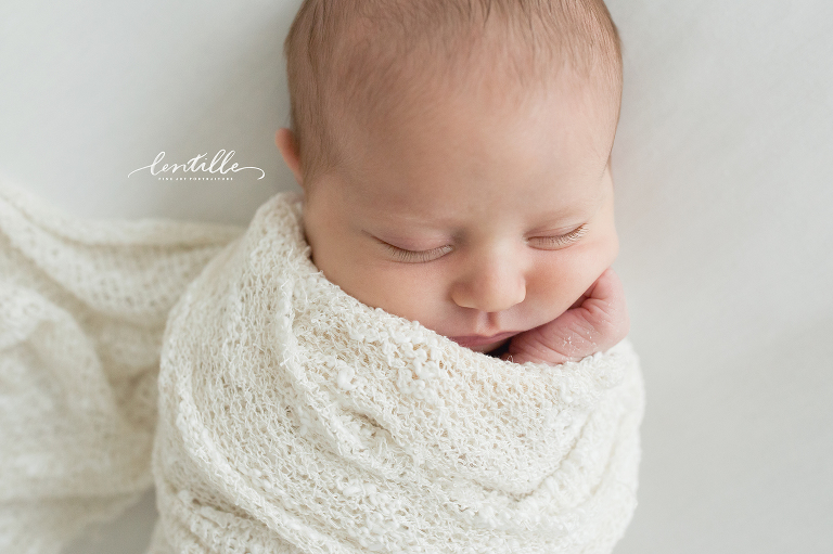 A baby sleeps wrapped in a blanket, captured by Lentille Photography, specializing in Houston Newborn Photography
