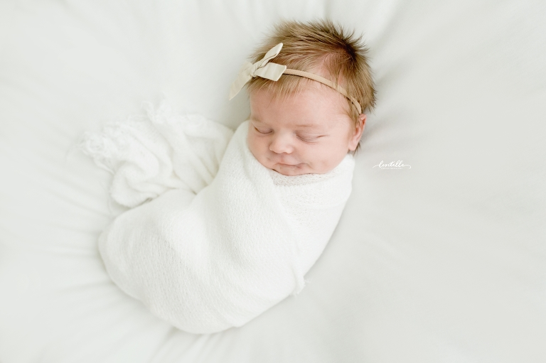 A sweet baby girl smiles in her sleep, catpured by Lentille Photography, specializing in Houston Newborn Photography