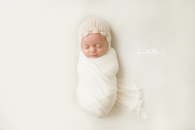 A baby sleeps wrapped in white captured by lentille photography a houston newborn