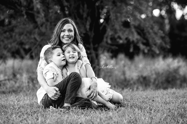 Two children sit in their mother's lap, captured by Lentille Photography, a Houston Family Photographer