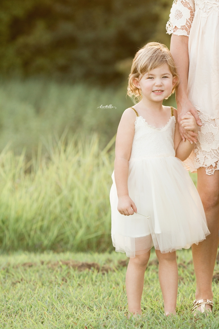 A little girl hold her mother's hand, captured by Lentille Photography, a Houston Family Photographer