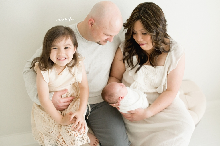 A family sits with their newborn, captured by Lentille Photography, a Houston Newborn Photographer