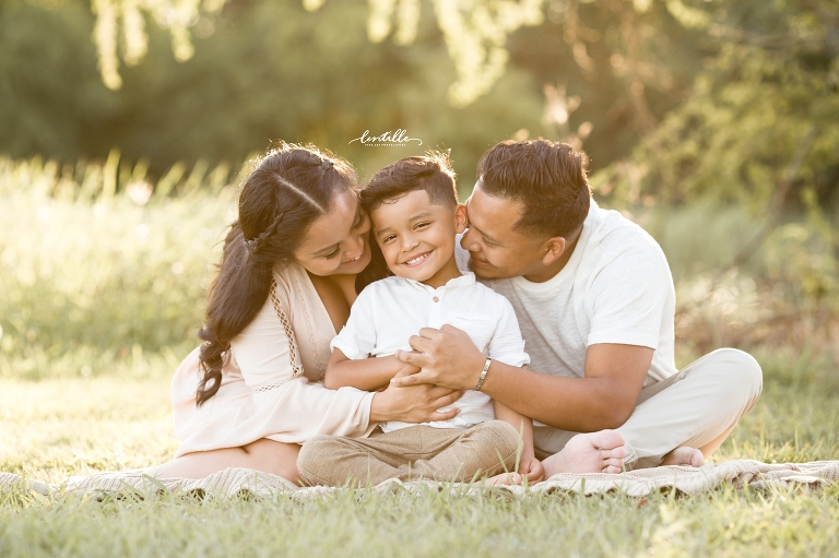 Parents kiss their son, captured by Lentille Photography, a Houston Family Photographer