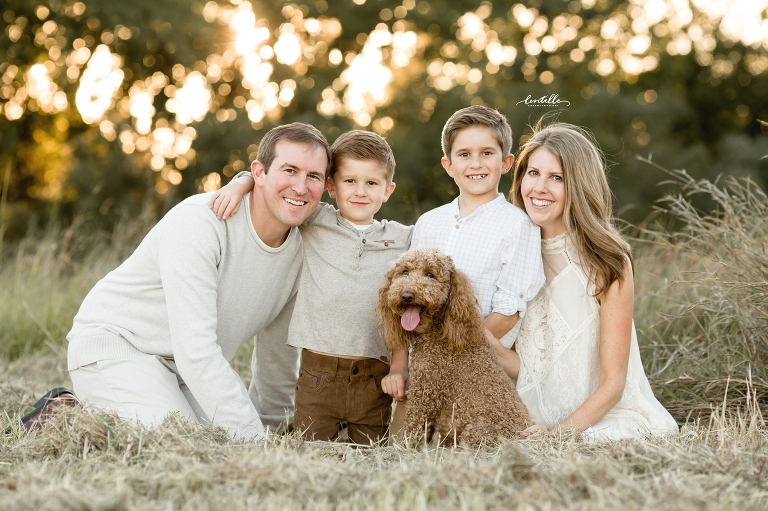 A family sits with their dog | Lentille Photography | Houston Family Photographer