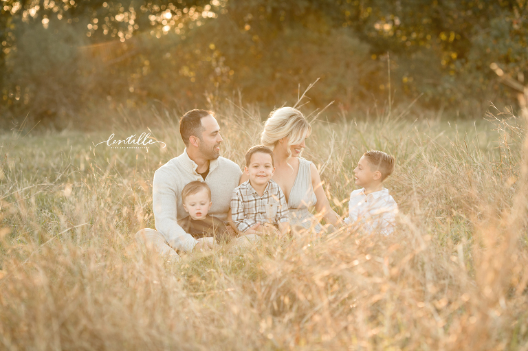 A family sits in a field | Lentille Photography | Family Photographer in Houston
