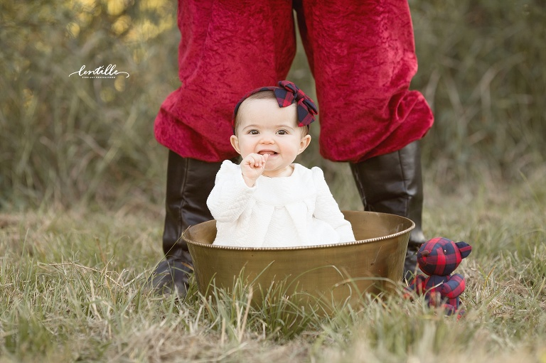 A baby sits at Santa's feet  | Lentille Photography | Best Houston Outdoor Santa Sessions