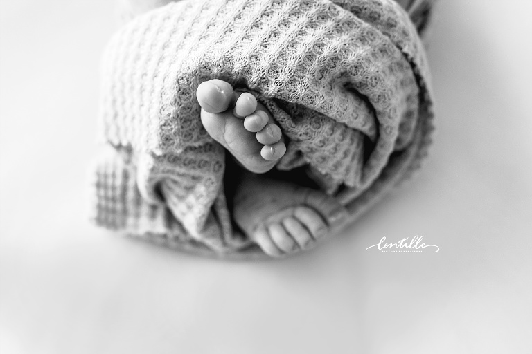 A baby's feet come out of a blanket | Lentille Photography | Newborn Photography in Houston