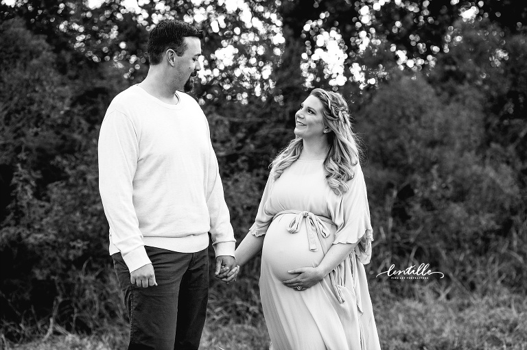 A pregnant woman looks at her husband | Lentille Photography | Houston Maternity Photographer