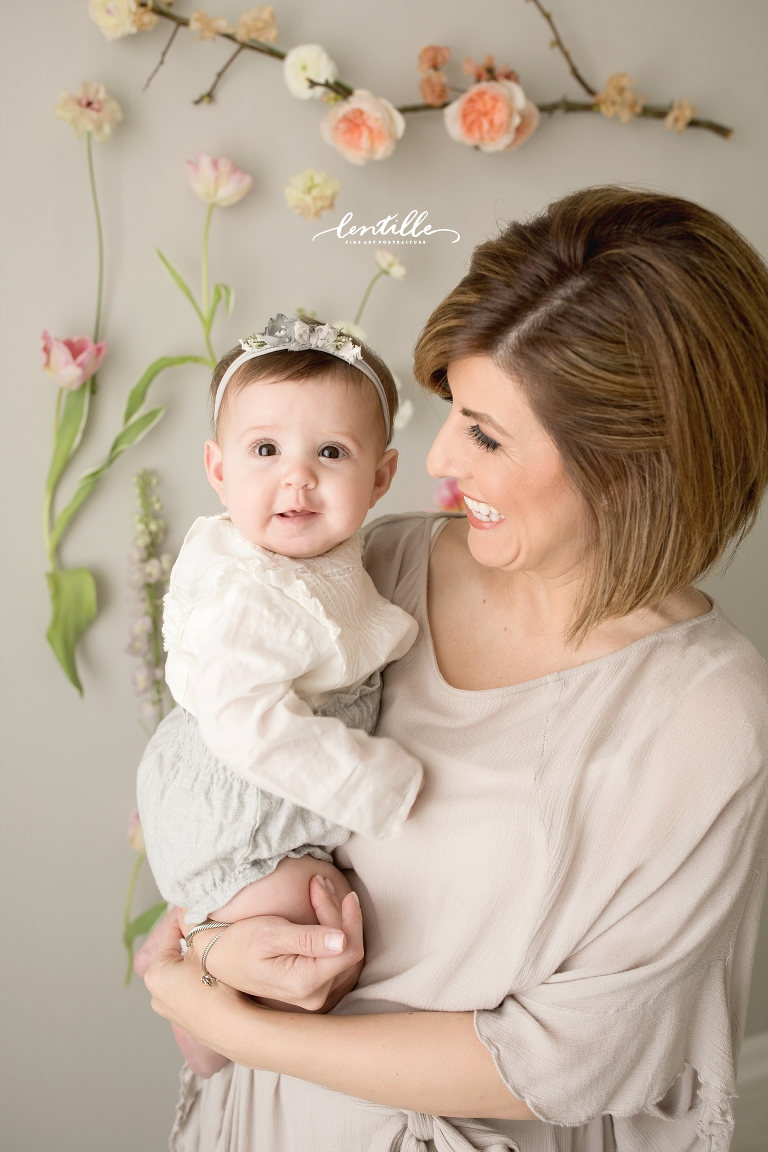 A mother holds her baby girl on her half birthday. | Lentille Photography