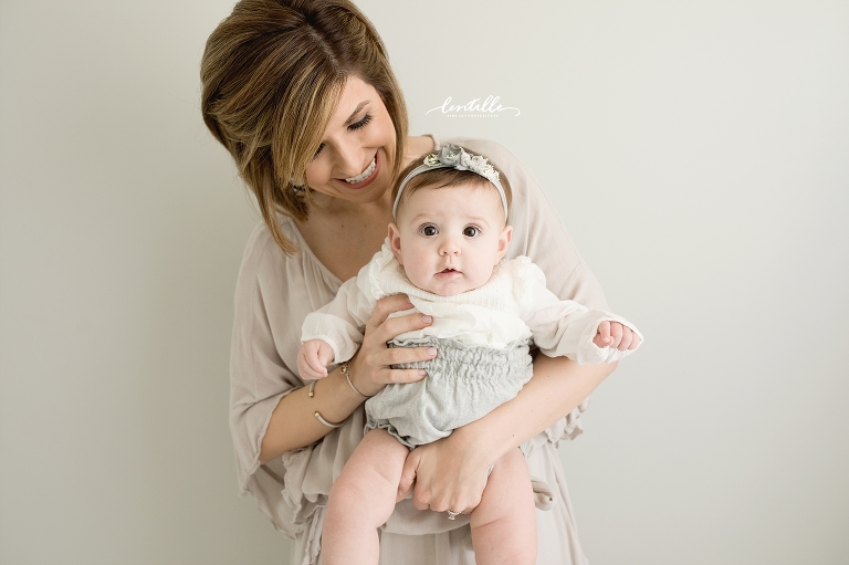 A baby girl looks at the camera for a half birthday photo shoot. | Lentille Photography