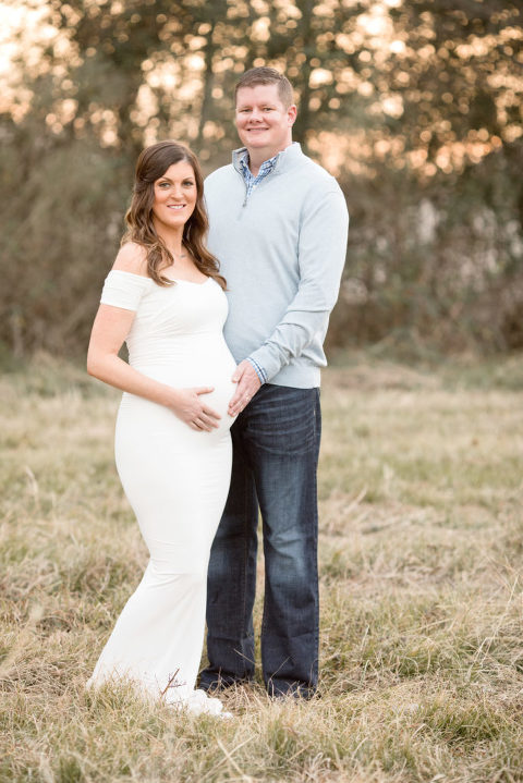 A man gently touches his pregnant wife's belly  | Lentille Photography | Maternity Sunset Session