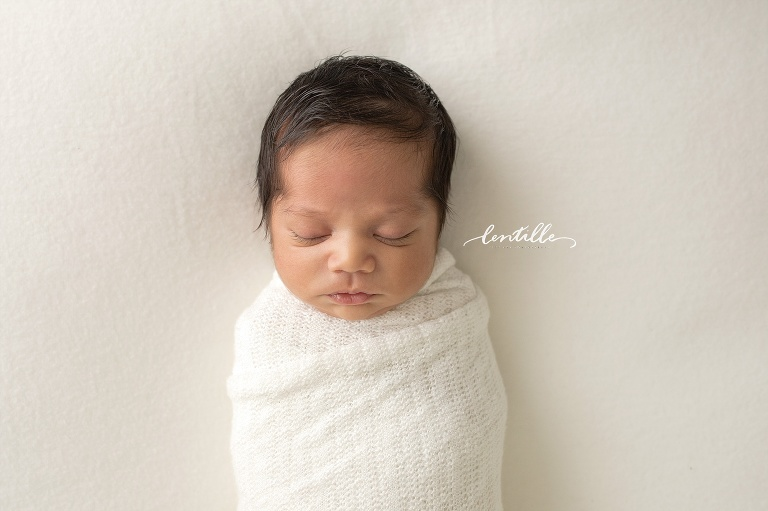 A newborn sleeps while swaddled.