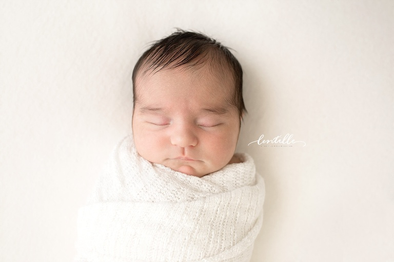 A baby sleeps while swaddled | Baby Photography In Houston
