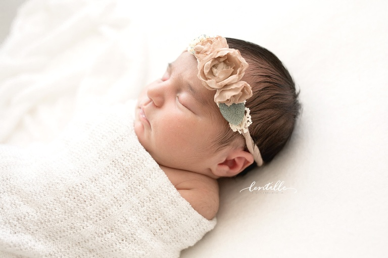 A new baby wears a flower headband.