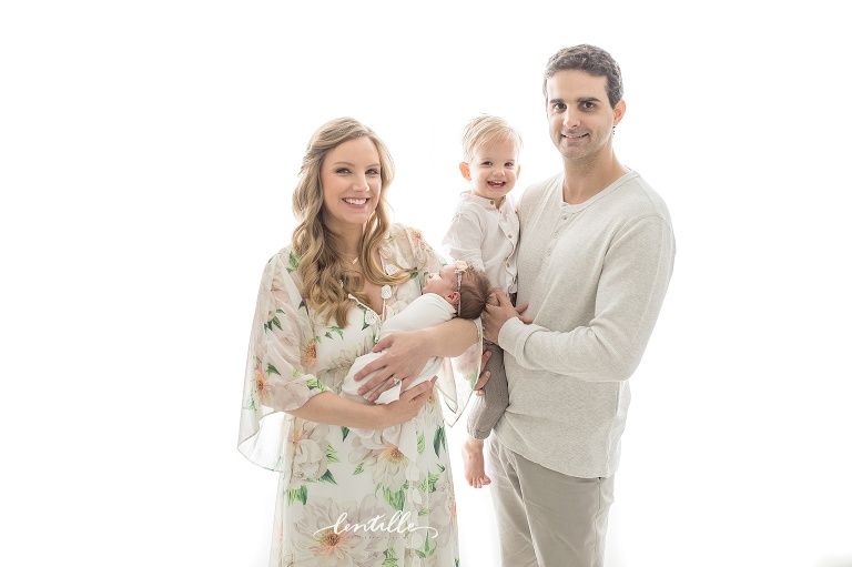 A family stands close in a white room | Houston Family Newborn Photos