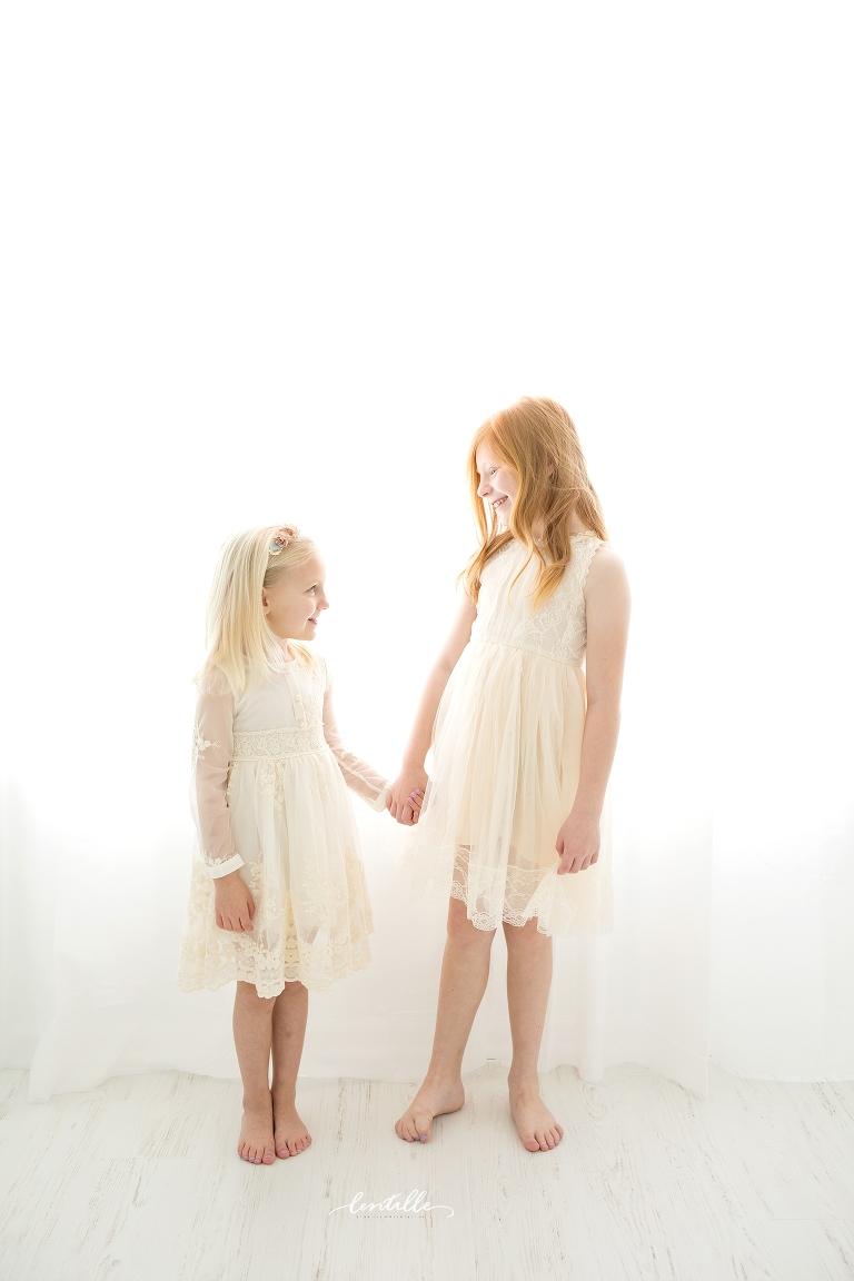 Two sisters hold hands, captured by a Houston Family Photographer