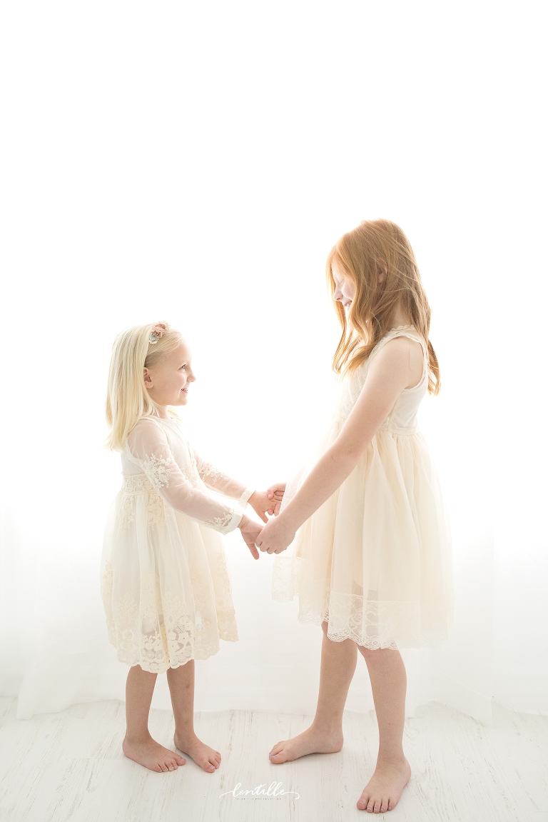 Sisters hold hands and smile.
