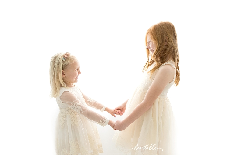 Two sister giggle together, captured by a Houston Family Photographer