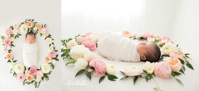 A newborn baby sleeps in a ring of flowers.