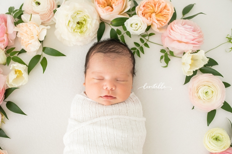 A baby girl sleeps with flowers above her head   Newborn Photography With Florals