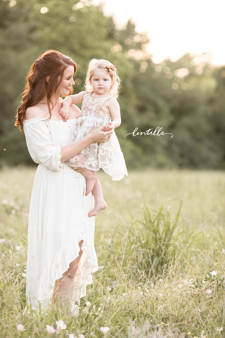 A woman wearing a long white dress holds her daughter.