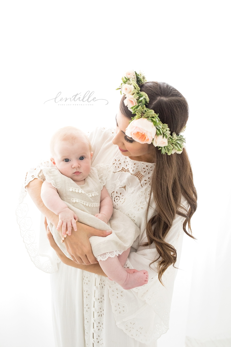 A woman wearing a flower crown gently holds her baby.