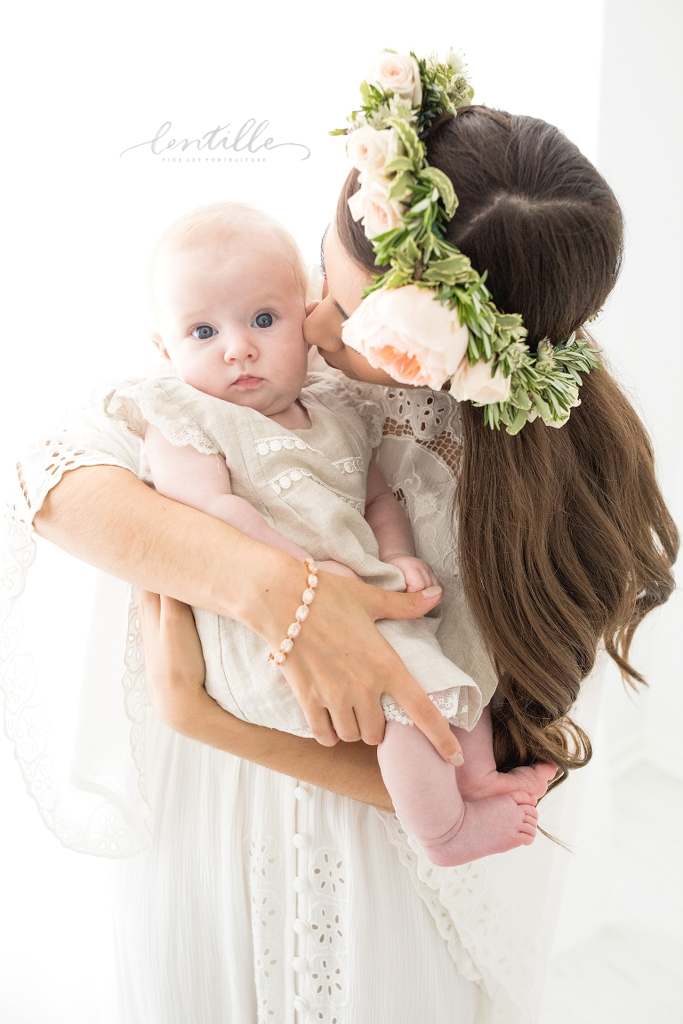 A mother kisses her baby girl on the cheek.