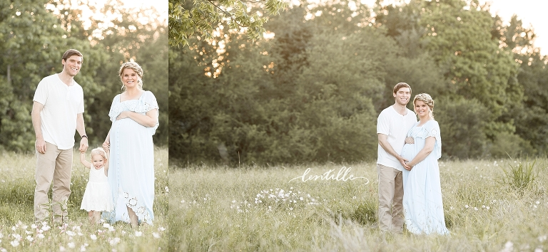 An expecting couple stands in a grassy field.