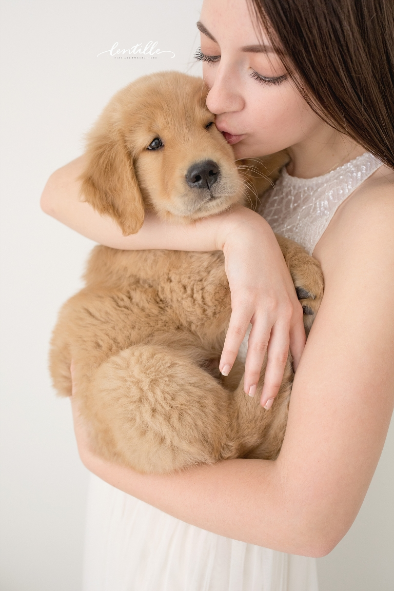 A woman snuggles her new puppy.