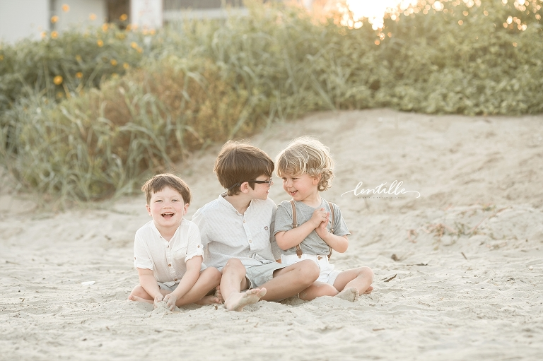 Three cousins play together in the sand.