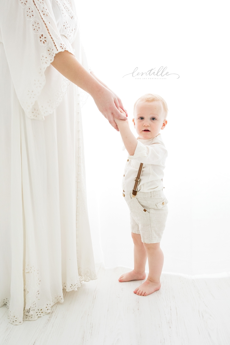 A toddler holds his mother's hands as they stand in a bright room.