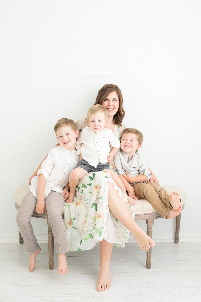 A mom sits with her three boys for some family photos.