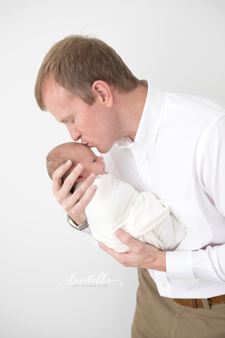 A father kisses his newborn on the head.