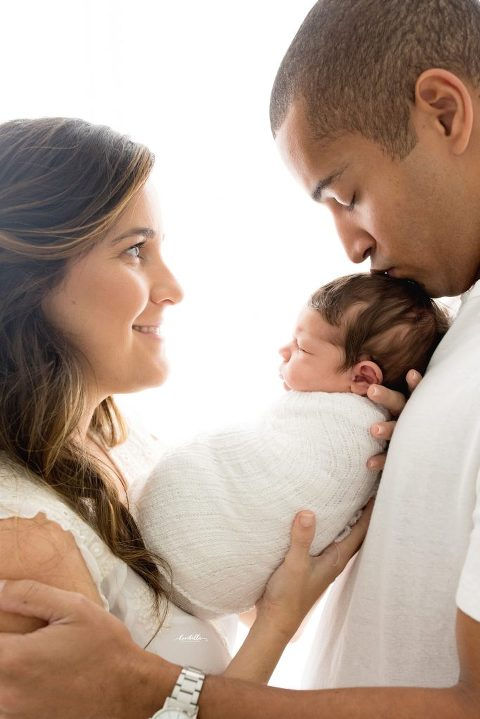 A woman holds her newborn up to her husband to kiss.