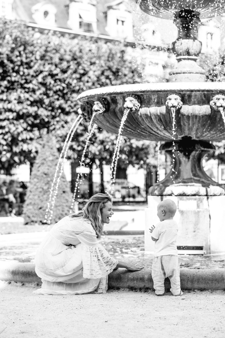 A mother kneels by her toddler next to a fountain in Paris.
