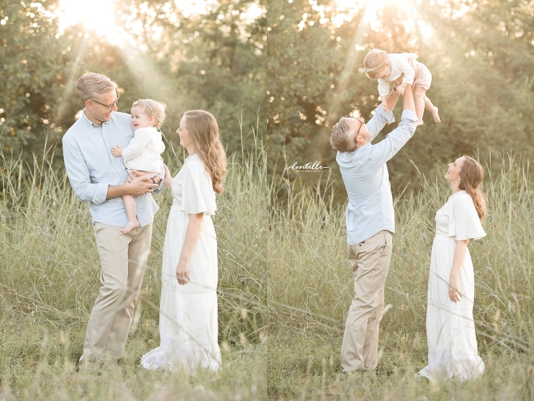 A dad raises his baby up into the air.